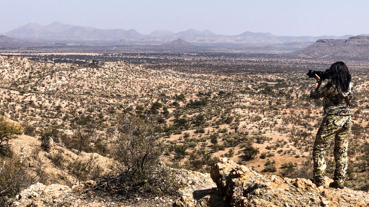 female hunter looking over arid land from high vantage