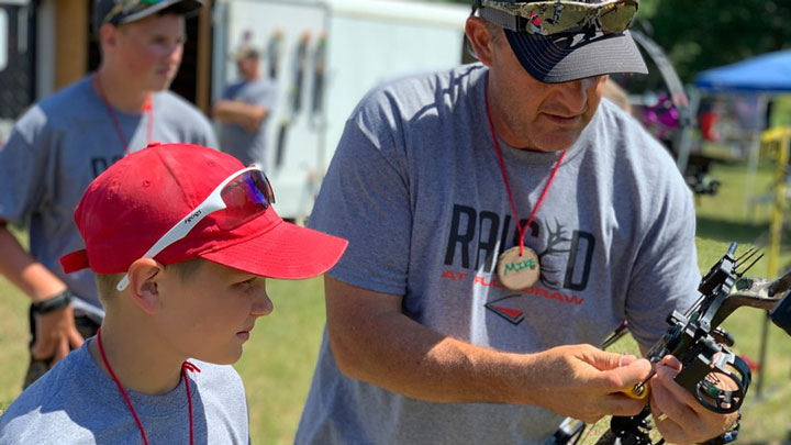 Volunteer helping youth at archery camp