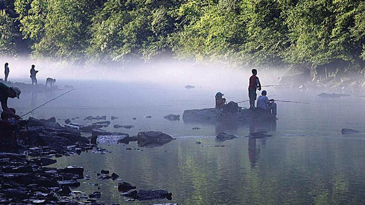 Children fishing on stream in early-morning mist