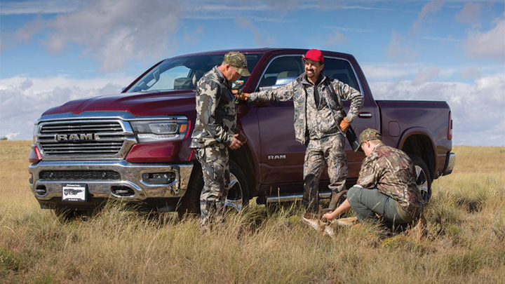 hunters gather at pickup truck in field