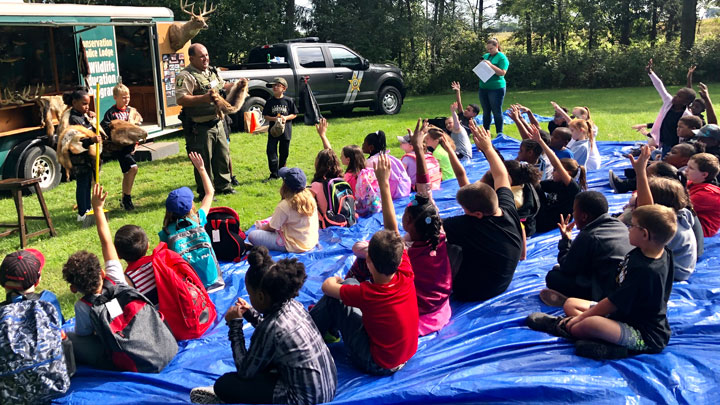 Children listen to Illinois Conservation Police Officer Steve Beltran discuss wildlife at a show-and-tell event.