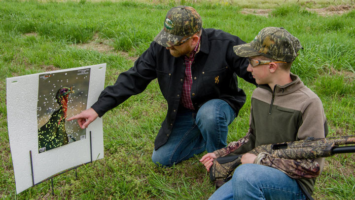 an adult instructs a young boy how to pattern a turkey-hunting shotgun