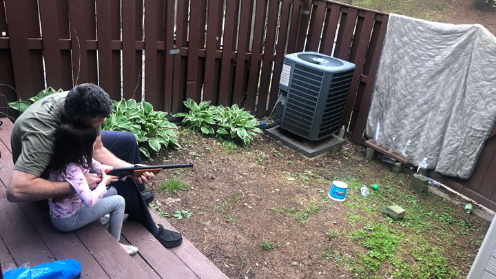 father teaches daughter how to shoot a bb gun