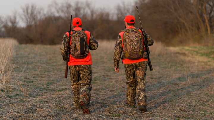 two hunters walk through the outdoors